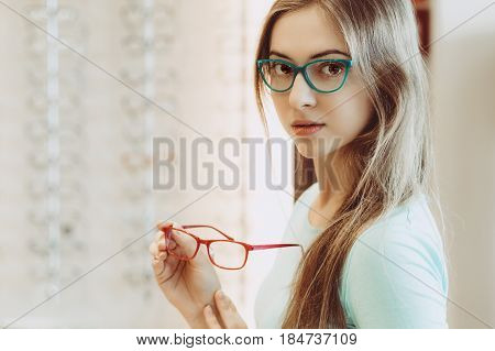 Young Woman Trying On Different Pairs Of Eyeglasses