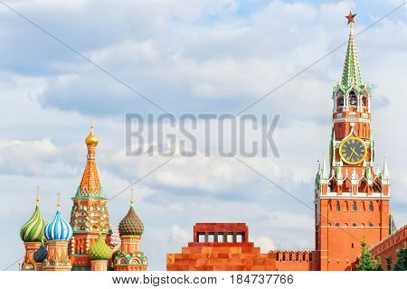 Red square Moscow Russia. Spasskaya tower of Kremlin with clock Lenin's Mausoleum and st. Basil Cathedral. Bright summer view sparse framing composition with copy space on the cloudy sky