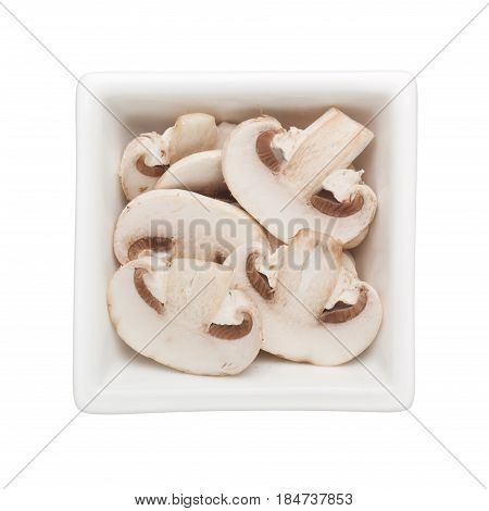 Sliced white button mushroom in a square bowl isolated on white background