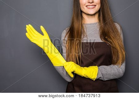 Close Up Of Young Woman Before Cleaning Wearing Rubber Gloves On Grey