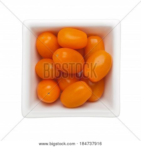 Orange colored cherry tomatoes in a square bowl isolated on white background