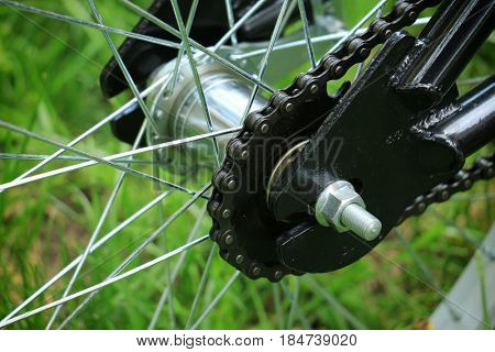 Closeup view of used bicycle single speed rear hub with wide chain and classic steel frame.