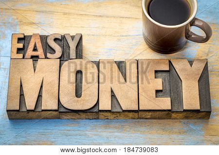 easy money word abstract in vintage letterpress wood type printing blocks with a cup of coffee