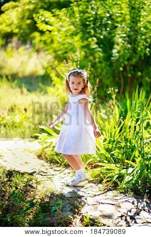 The child turned walking on the trail. Good girl in a white dress walks among the green bushes and grasses. A small child for a walk.