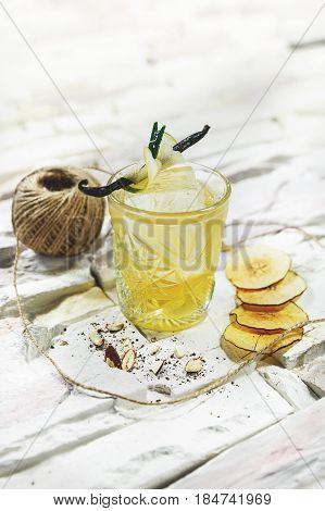 Bright yellow alcohol cocktail garnished with pear and vanilla on white background