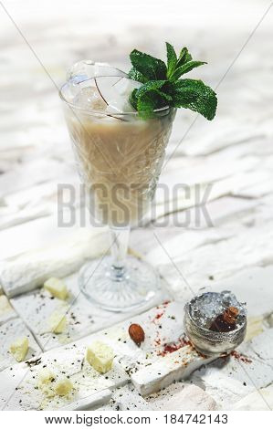 White alcohol cocktail with Protein foam garnished with cheese, coconut and mint on white background