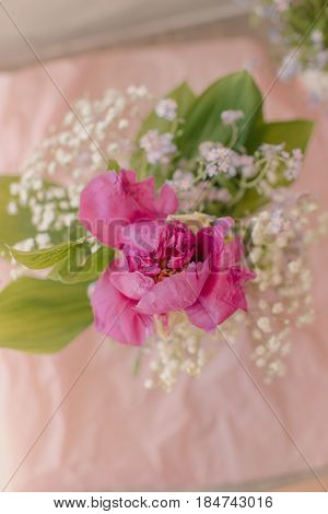 Very tender spring bouquet of lilies of the valley and forget-me-nots and peonies