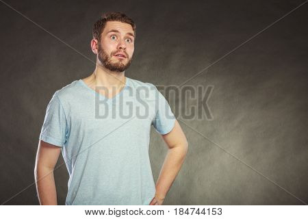 Portrait of scared afraid shocked handsome man in shirt. Young guy posing in studio on black.