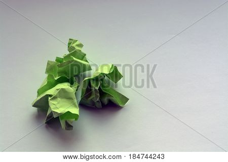 Wrinkled Green Paper On A White Table. Crumpled Notes Of Failed Sketches