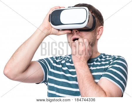 Amazed man wearing virtual reality goggles watching movies or playing video games, isolated on white background. Surprised male worried and scared making face looking in VR glasses.