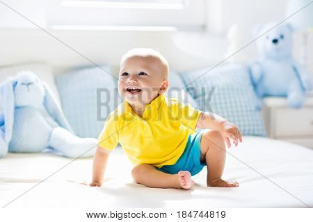 Baby Boy Playing On Bed In Sunny Nursery