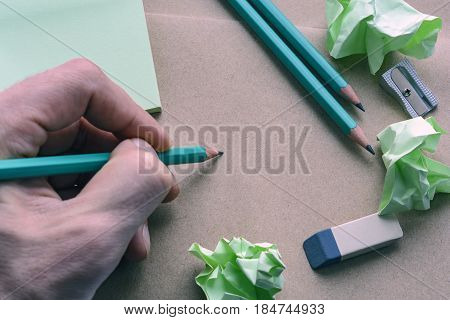 Male Hand With A Pencil, Sharpener, Eraser, Stickers, Brown Paper With Crumpled Sticky Notes, Creati