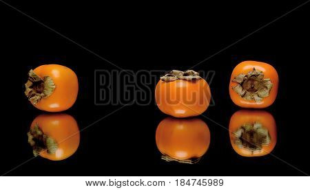 persimmon on a black background with reflection closeup. horizontal photo.