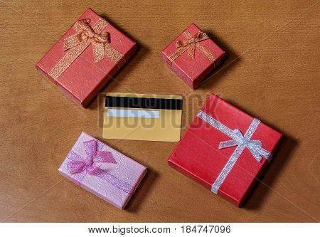 Credit card and gift boxes on wood background