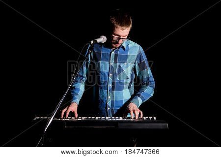 Musician Playing On Keyboard Electric Piano And Singing On Dark. Musician Concept
