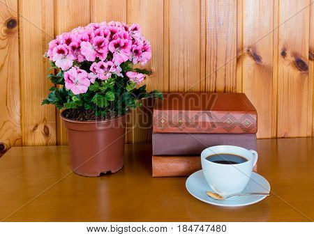 Books cup of coffee and pelargonia flower on wooden table over wooden background