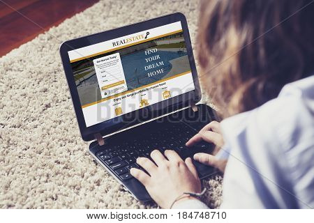 Woman looking for home in a real estate website with a laptop while lying at home.