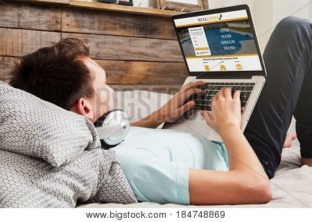 Man looking for home in a real estate website with a laptop while lying at home.