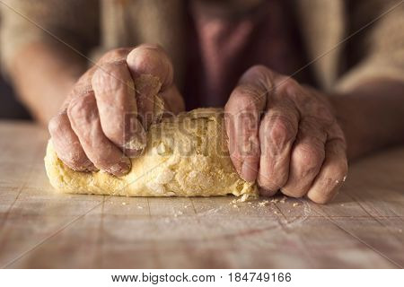 Detail of an elderly woman's hand kneading dough while making homemade pasta. Selective focus on the hand and dough