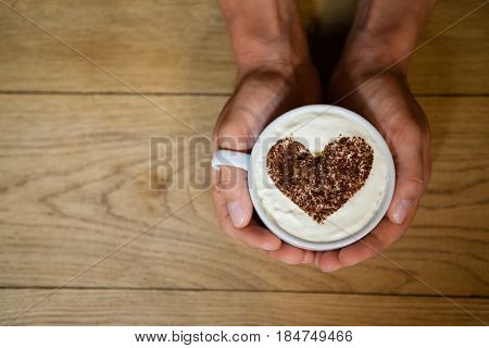 Cropped image of person holding coffe cup with frothy art at wooden table