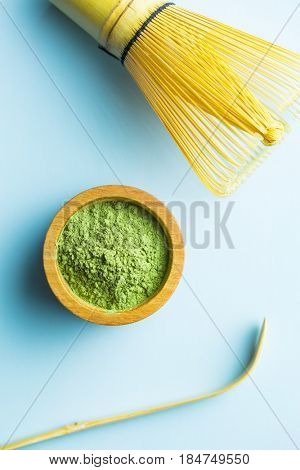 Green matcha tea powder, bamboo whisk and bamboo spoon on blue background.