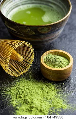 Green matcha tea powder with bamboo whisk , spoon and bowl. Tea preparation accessories.