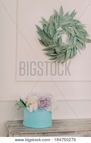 On the wall hangs a green wreath of twigs and stands on a table box with flowers