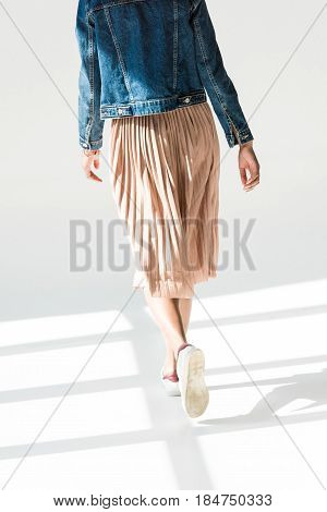 Rear view low angle shot of woman in beige skirt and denim jacket walking in white studio