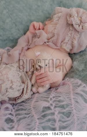 On a bed in lace a baby's hand holds a teddy bear