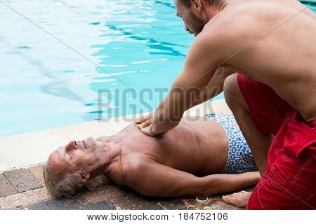 Lifeguard pressing chest of unconscious senior man at poolside