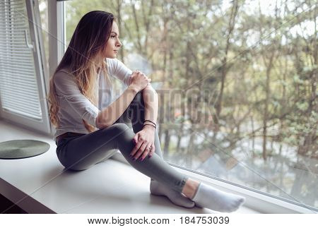 Beautiful melancholic woman sitting on window ledge at home