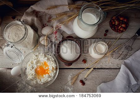 Fresh dairy products. Milk cottage cheese sour cream and wheat on rustic wooden background. Organic farming dairy concept. Top view flat lay