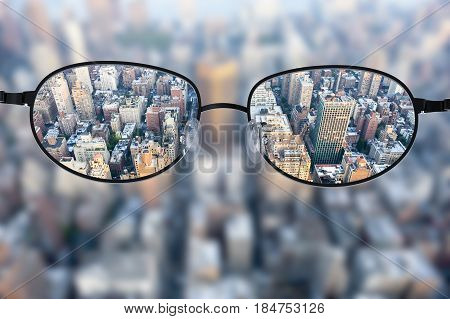 Clear cityscape focused in glasses lenses with blurred cityscape background