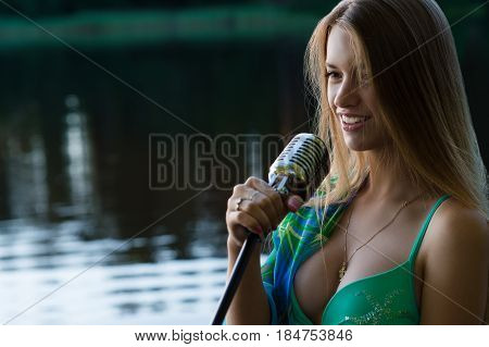 smiling teenager singer girl with retro microphone