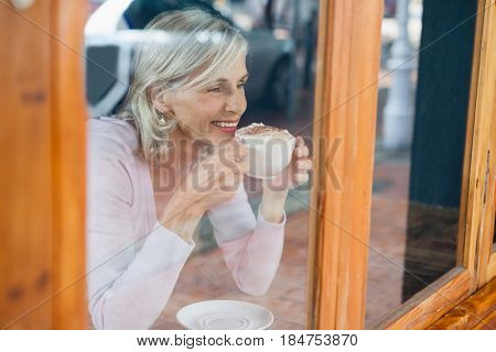 Smiling senior woman drinking coffee while sitting by table at cafe shop