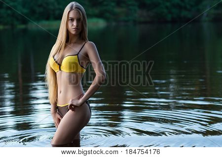 slender girl teenager in fashionable swimsuit standing in water