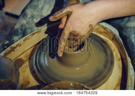 Woman potter works with clay on potter wheel, hands close up
