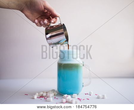 Woman is pouring coffee in cup of colored blue milk. Milk shake cocktaill frappuccino. Unicorn coffee unicorn food.