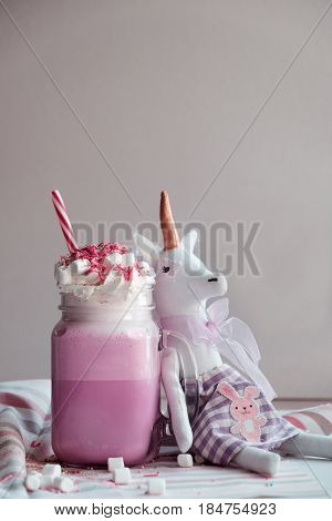 Toy unicorn with pink milk shake with cream marshmallow and colorful decoration. Milk shake cocktail. Unicorn coffee. Unicorn food