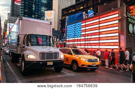 NEW YORK CITY -JUNE 21: People and traffic in front of famous american led flag of The New York City Police Department in Times Square, on March 21, 2016 in Manhattan, New York City, USA.
