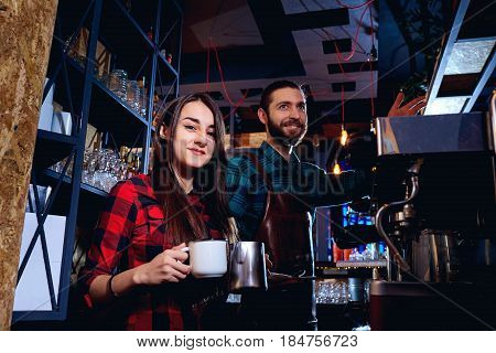 Bartender and  waiter are working behind counter in the bar.