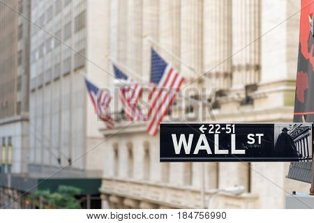 Wall street sign and New York Stock Exchange background on June 25, 2016 in New York, NY.