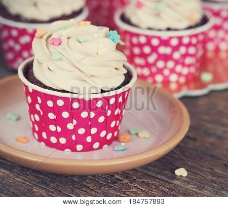 Chocolate cupcake with chocolate mousse cream icing on grunge dark wooden background Toning