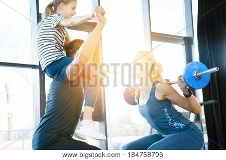 Woman Workout With Barbell While Man Having Fun With Daughter On His Shoulders