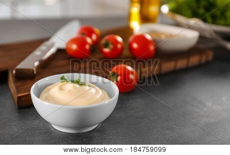 Delicious mayonnaise in bowl with ingredients on kitchen table