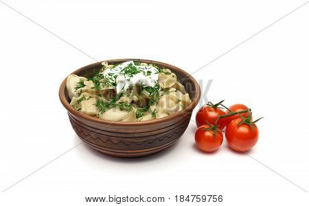 dumplings with sour cream and tomatoes on a white background. horizontal photo.