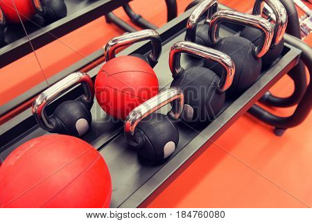 fitness, sport, sports equipment, weightlifting and bodybuilding concept - close up of kettlebells and medicine ball in gym