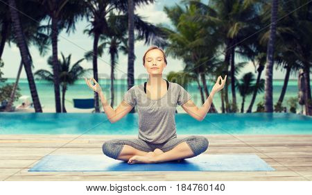 fitness, sport, people and healthy lifestyle concept - woman making yoga meditation in lotus pose on mat over hotel resort pool on tropical beach background