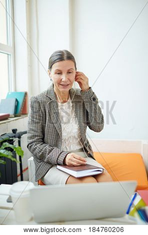 Portrait of beautiful mature employee listening to music with headphones while working on promising project with help of laptop