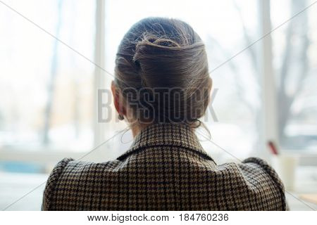 Unrecognizable woman with elegant hair bun wearing houndstooth jacket sitting at panoramic window, back view